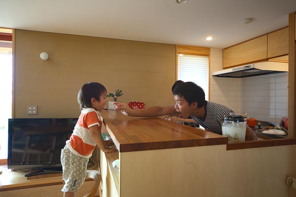 姫路市の木の家 対面キッチン越しに触れ合うご主人とお子さん