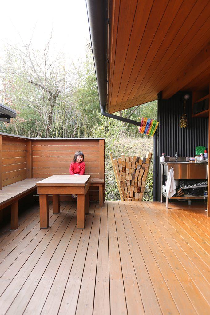 姫路市の木の家 ウッドデッキのベンチに腰掛けるお子さん
