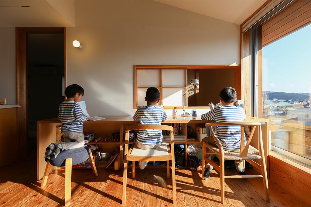 姫路市の木の家 フリースペースの勉強机に仲良く座る三兄弟