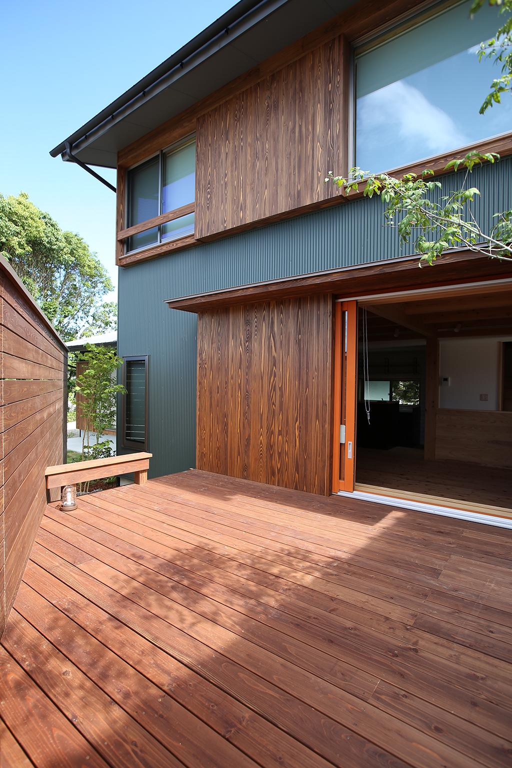 明石市の木の家 グリーンの外壁と濃茶色の杉板が落ち着いた雰囲気の外観